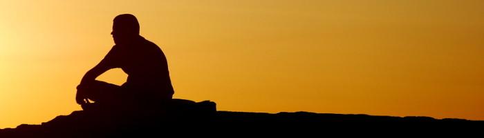 Man performing Guided Chakra Meditation at sunset