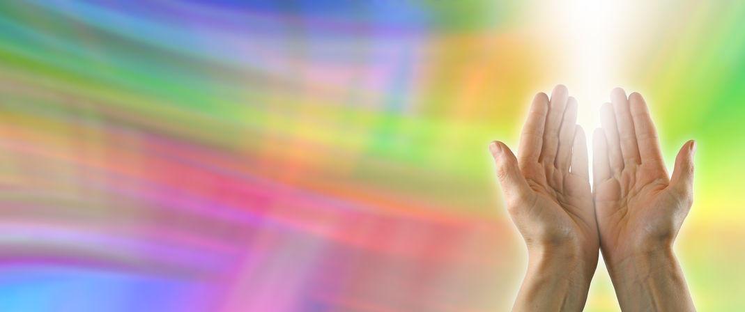 Hands receiving reiki energy during reiki attunement