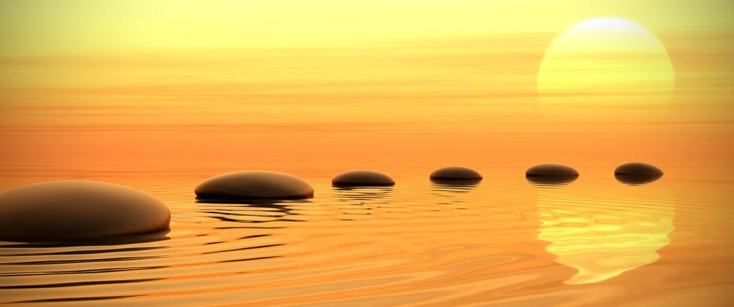 Calming image of rocks emerging from the sea as sunset. Imagery for Chakra meditation