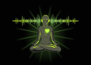 A woman sitting in lotus position listening to Guided Chakra meditation for the Heart Chakra